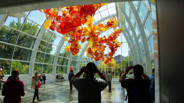 Tourists admire the Glass flowers in the conservatory sunlight of the Chihuly Garden and Glass Museum, Seattle, Washington