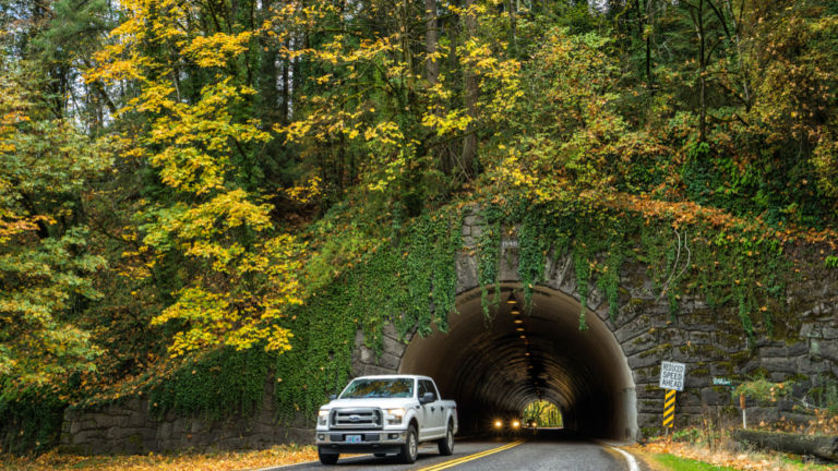 Vehicles drive through a stone tunnel leading to the entrance of Forest Park, the largest park in Portland, Oregon.